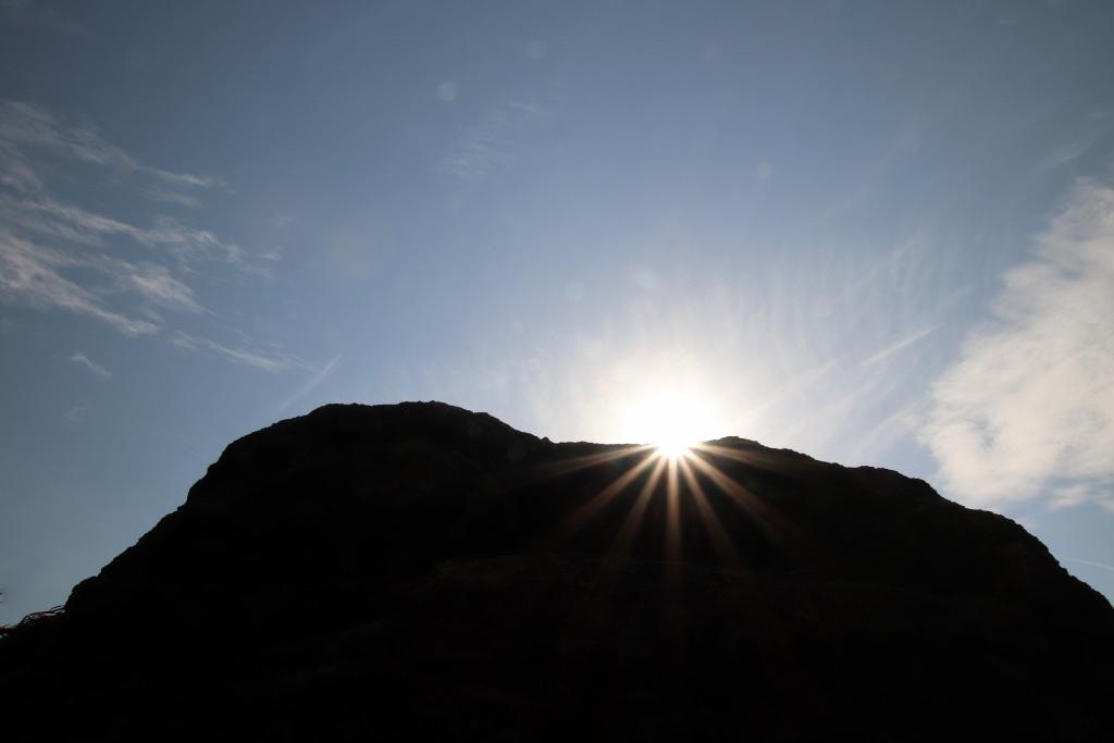 sun peaking over a big rock