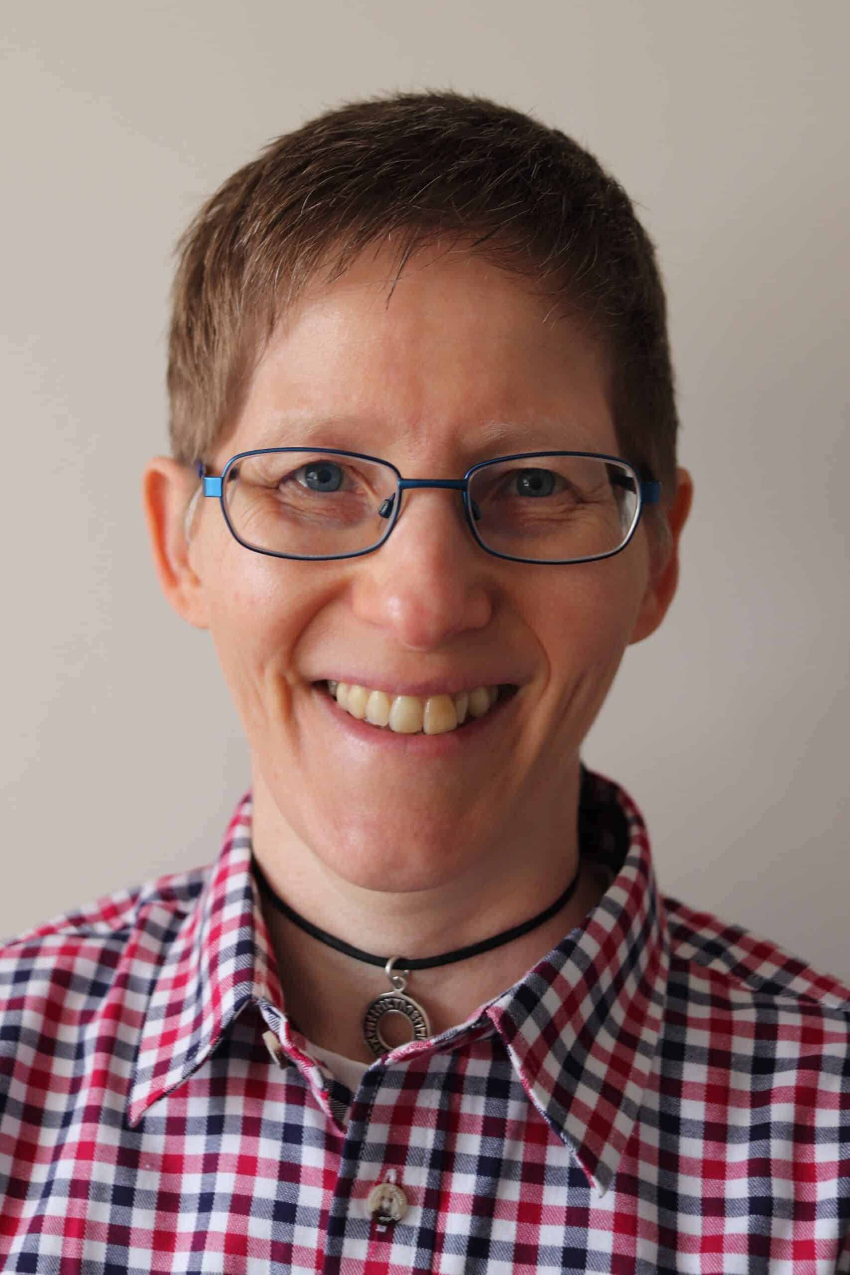 Luan Baines-Ball Counselling and psychotherapy Luan has short light brown hair and is wearing blue glasses and a navy red white check shirt